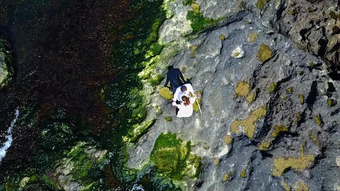 Aerial Of Couple On Cliff next to sea Live Action