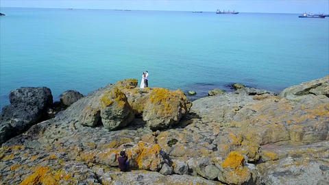 Aerial Of Couple On Cliff next to sea and photographer shoot them
