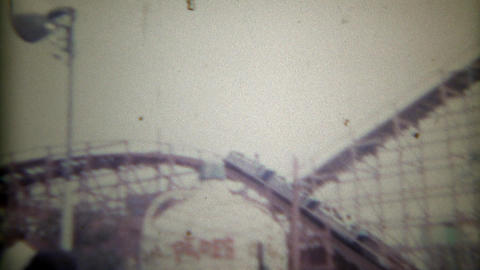 1965: Vintage carnival rollercoaster ride metal painted tracks fast screw turn.  Footage