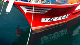 Spain Gran Canary Mogán 024 bow of red fishing boat in smooth water Footage