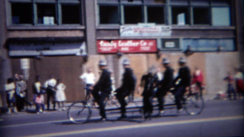 1964: Old timey police officer riding 5 person bike at parade Footage