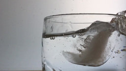 Ice Cube Fall Into Glass Of Water stock footage