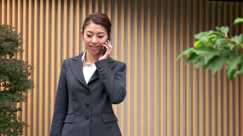 Confident Asian Woman Talking On Mobile Phone Near Office Building Footage