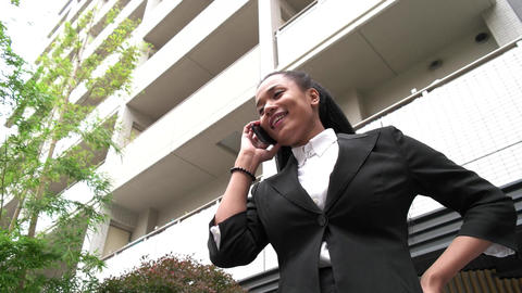 Multiethnic Young Woman Talking On Telephone Smartphone Near Office Skyscrapers Footage