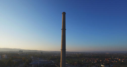 Aerial view of abandoned industrial buildings and chimney at sunset Footage
