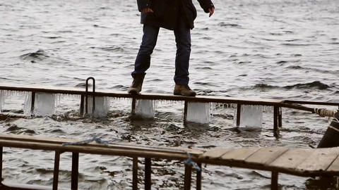 Man walking dangerously on a narrow icy pier GIF
