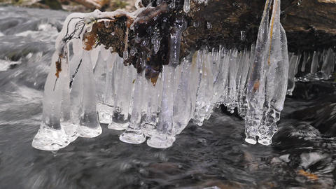 Detail of shinning icicles hanging above cold water of winter mountain river. Gl 영상물