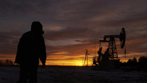 Worker Silhouette in Hood Comes to Pumpjack against Sunset Footage