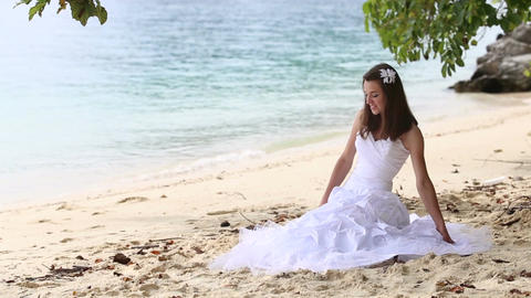 Longhaired Bride Sits on Sand and Stands up against Sea and Island Footage