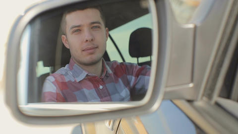 Man looking at camera through rear view mirror, man driving car, driver Footage