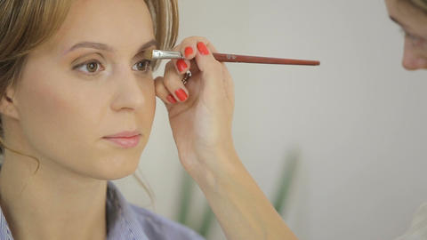 Close up shot. Professional make-up artist applies eye shadow to eyelid of model Footage
