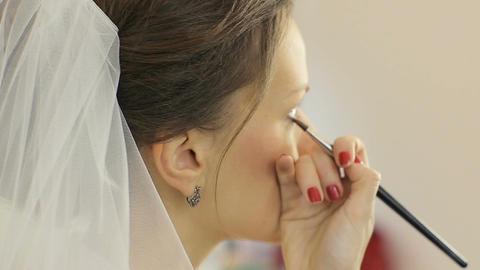 Make up artist putting on mascara on model's eyes. Eye make up Live Action