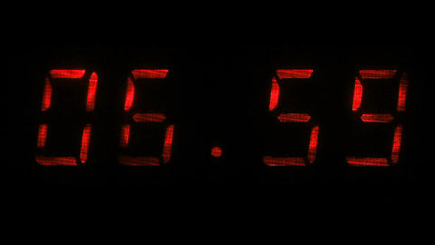 Digital clock shows time of 06 hours 59 minutes to 07 hours 00 minutes Footage