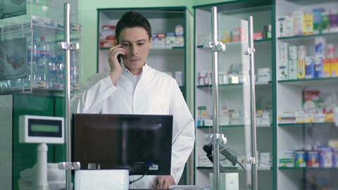 Male pharmacist communicating on phone in pharmacy Footage