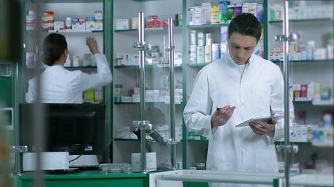 Pharmacists checking medicines at pharmacy Footage