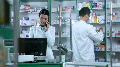 Beautiful female pharmacist taking orders on phone Footage