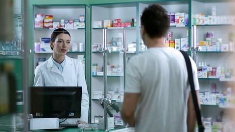Pharmacist giving advice to customer on medication Footage