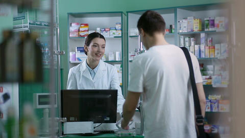 Smiling pharmacist giving client pills in pharmacy Footage