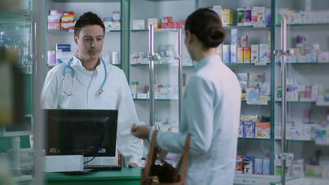 Girl giving prescription to pharmacist in pharmacy Footage