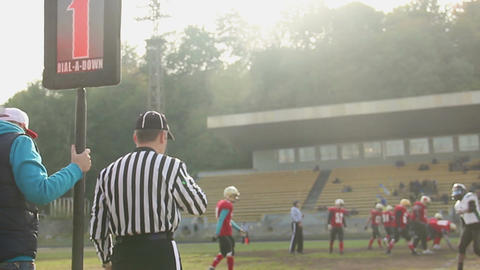 Referee supervising amateur American football match, making first down hand sign Footage