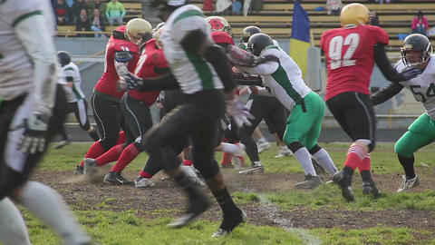 Opposing football teams start massive attack, tackle player with ball, scrimmage Footage
