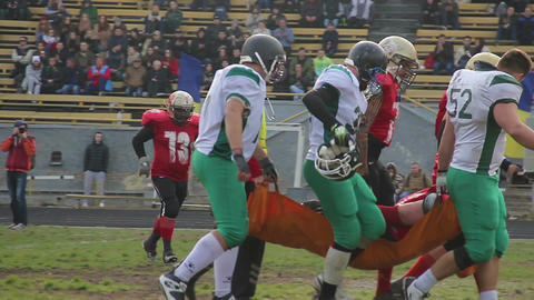 Supportive football players carrying injured teammate on stretcher, togetherness Footage