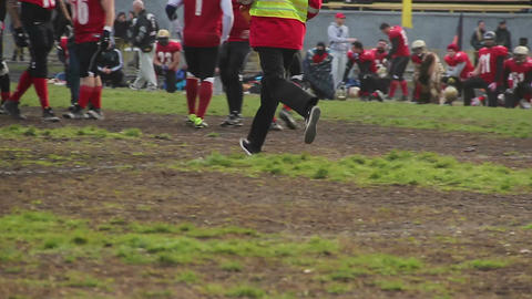 Doctors running gridiron field to give first aid to football player with trauma Footage