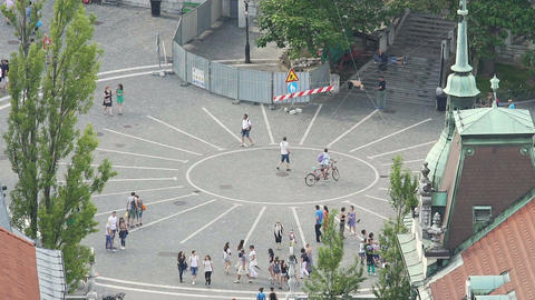 Small European city square, people walking, riding bicycles Footage