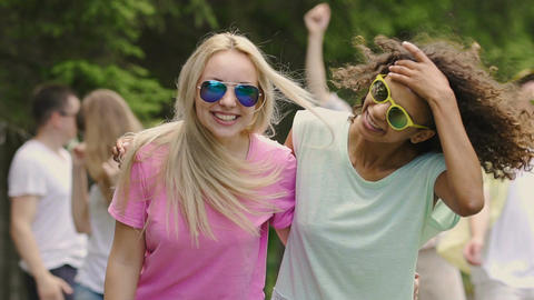 Students having party in park, two beautiful multiracial girls dancing, smiling Footage