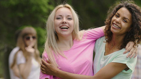 Young beautiful women hugging, smiling at camera, group of young people partying Footage