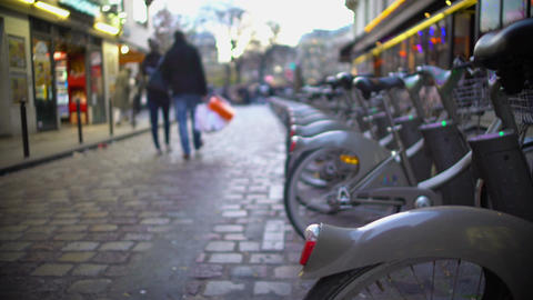Urban life, bicycles for rent, people walking down the street, enjoying weekend Footage