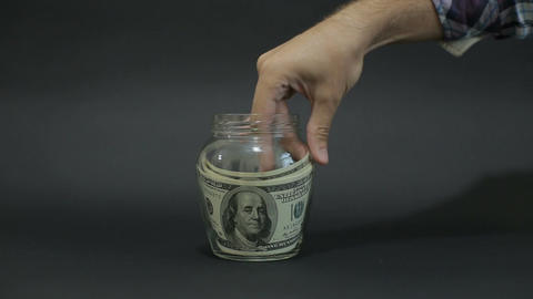 Man Puts American Dollar 100 into a Glass Jar for Storage. Slot glass jar on bla Footage