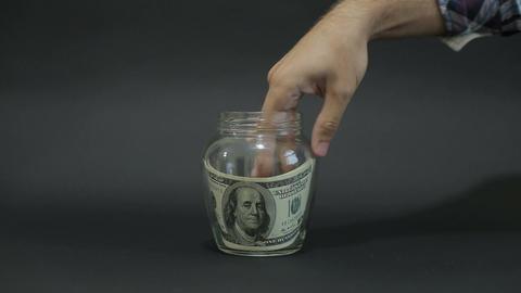 American Dollar 100 in the Glass Jar for Storage. Slot glass jar on black backgr Live Action