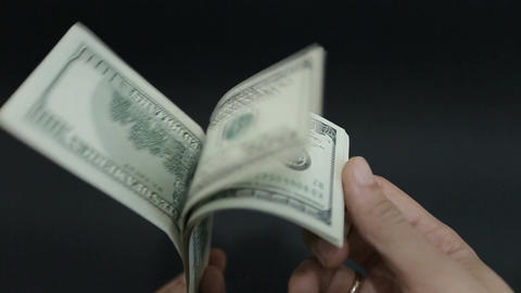 A large stack of hundred dollar bills on a table gradually blows away to nothing Footage