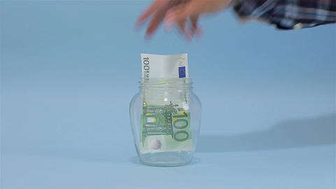 Man Puts Euro 100 into a Glass Jar for Storage. Slot glass jar on light-blue bac Footage