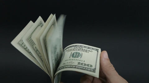 A large stack of hundred dollar bills on a table gradually blows away to nothing Live Action