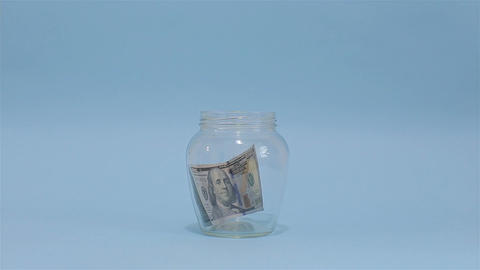 Man Puts American Dollar 100 into a Glass Jar for Storage. Slot glass jar on lig Footage