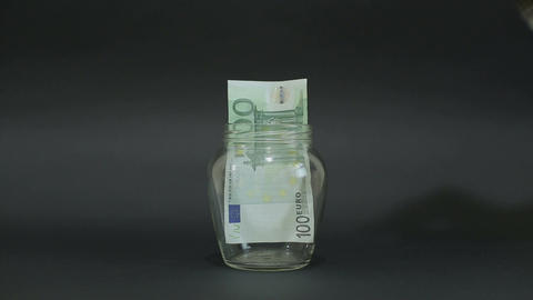 Man Puts Euro 100 into a Glass Jar for Storage. Slot glass jar on black backgrou Footage