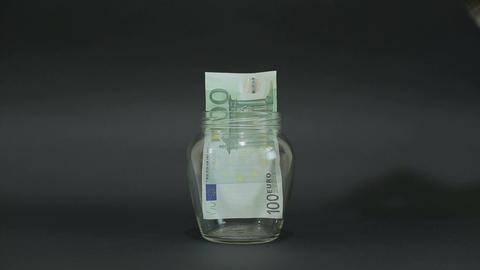 Man Puts Euro 100 into a Glass Jar for Storage. Slot glass jar on black backgrou Footage