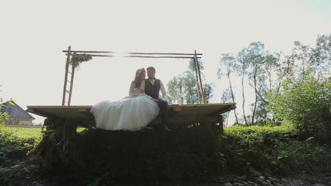 Happy bride and groom sitting hugging and Kissing near river Footage