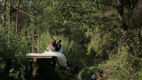 Young and in love wedding couple sits hugging near river Footage