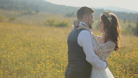 Beautiful bride and groom gently hugging in a field in the mountain