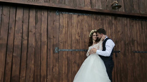 Happy bride and groom laughing near wooden ambar at the wedding walk Live Action