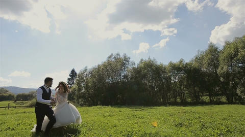 Charming wedding couple running on the grass in the mountains Live Action