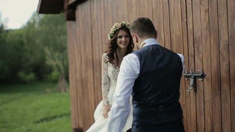 Happy bride and groom running and laughing near wooden ambar at the wedding walk