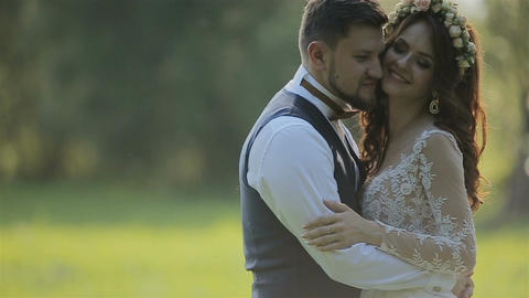 Close-up of Beautiful bride and groom gently hugging in a field in the mountain