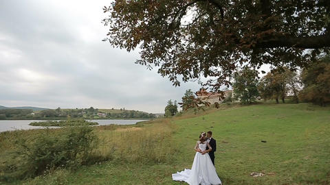 Beautiful bride and groom gently hugging in a grass near the lake and the old ca