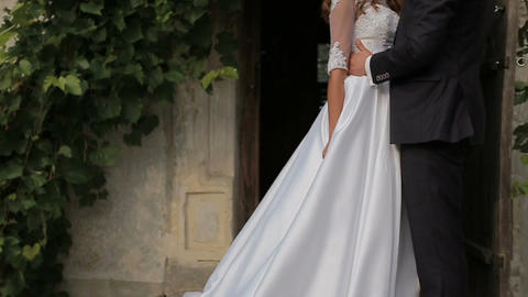 Close-up of Beautiful bride and groom gently hugging in the courtyard of the old