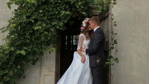 Beautiful bride and groom gently hugging and Kissing in the courtyard of the old