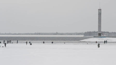 Many winter fishermen angling on ice of water storage reservoir Footage